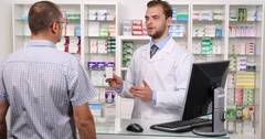 Pharmacist Man Talking with Patient About Medicine Drug Instructions in Pharmacy Stock Footage