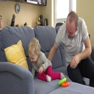 Playful father have fun with baby girl on sofa at home. Man tickle toddler girl Stock Footage