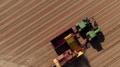 Drone shot of combine harvester collecting potatoes in field Stock Footage