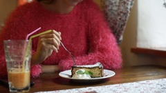 Girl in pink, fluffy sweater sitting in the cafe and eating delicious cake Stock Footage