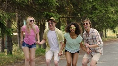 Four multiracial friends jumping together in park at open-air music festival Stock Footage
