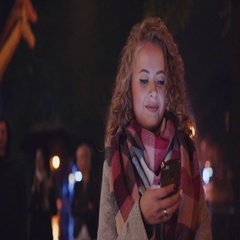 Curly blonde girl walking down the street and texting a message, smiles and Stock Footage