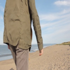 A middle aged man with a beard wearing grey pants, green jacket and yellow boots Stock Footage