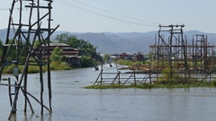 Long boats float between stilted houses on Inle Stock Footage