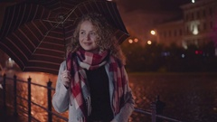 Curly stylish blondie dreaming under the umbrella in the city center. Beautiful Stock Footage