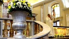 Catholic priest saying homily behind flower vase Stock Footage