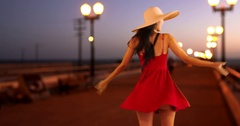 Young white girl dances on the pier in a red sun dress and floppy hat Stock Footage