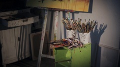 Beautiful woman artist paints with oil painting. dirty workshop Stock Footage
