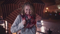 Blonde curly girl in a warm grey coat and colorful scarf standing under the Stock Footage