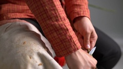 View of craftsman cleans withy from bark, close-up Stock Footage