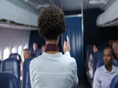 Female flight attendant points out aircraft exits in slow motion 4K Stock Footage