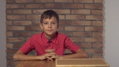 Child sitting at the desk holding flipchart with lettering how are you on the Stock Footage
