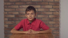 Child sitting at the desk holding flipchart with lettering staff on the Stock Footage