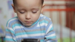 Little boy playing with a smartphone gadget Stock Footage
