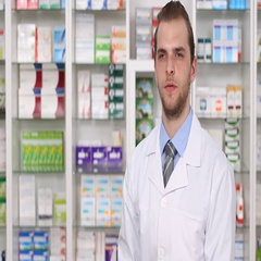 Serious Experienced Pharmacist Man Looking and Talking Camera in Pharmacy Shop Stock Footage