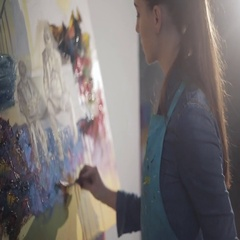 Artist working on an oil painting. View of canvas. Soft light from a window Stock Footage