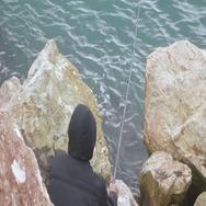 Fisherman on sea on rocks Stock Footage