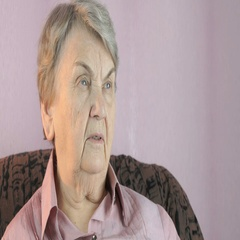 Aged woman 80s sitting indoors covers face hands Stock Footage