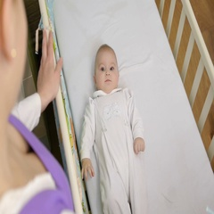 45-year mother stands next to the playpen and looks into small child Stock Footage