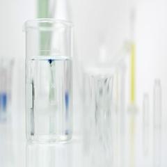 Blue drops falling into clear liquid in glass beaker. Stock Footage