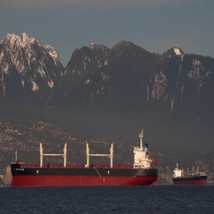 Container ships in English Bay framed against the mountains in West Vancouver Stock Footage