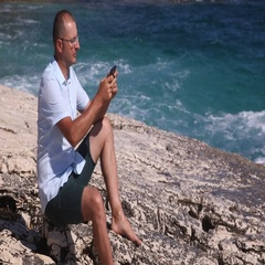 Adult Man Profile Sending Message on Mobile Phone Besides the Seashore View Day Stock Footage
