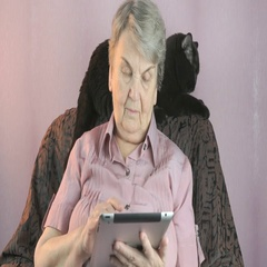 Elderly woman sits at armchair next to black cat Stock Footage