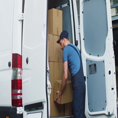 Young and Smiling Delivery Service Man Takes Cardboard Box from his Cargo Van an Stock Footage