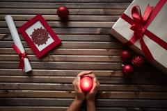 Human hands holding red burning candle being surrounded by xmas symbols Stock Photos