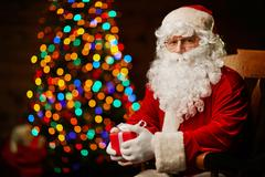 Santa Claus with gift-box looking at camera with sparkling xmas tree on backgrou Stock Photos