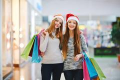 Two happy shopaholics looking at camera at Christmas sale Stock Photos