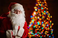 Happy Santa with sack of gifts on background of sparkling fir-tree Stock Photos