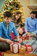 Teenage boy tying knot on top of gift-box Stock Photos