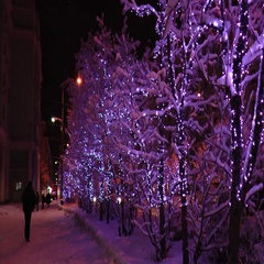 People walk along a snowy street at night at led holiday lighting. Stock Footage