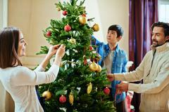 Happy couple and their son decorating xmas tree at home Stock Photos