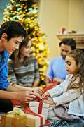 Little girl helping her brother tie knot on xmas gift-box Stock Photos