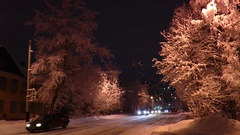 Snow-covered trees and a city street on a background of dark sky. Stock Footage