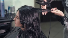 Hairstylist curling the long black hair of a female client using a heated hair Stock Footage