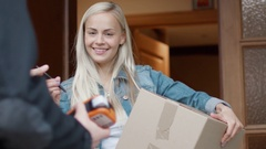 Smiling Woman Receives Postal Package after Signing Electronic Signature Device  Stock Footage