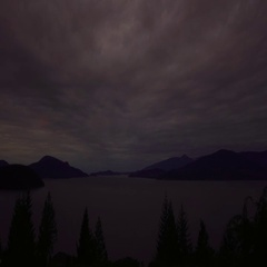 Dramatic timelapse of brightening clouds sweeping over Howe Sound at sunrise  Stock Footage