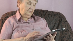 The old woman holding the silver tablet computer Stock Footage