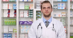 Serious Pharmaceutist Male Looking Camera and Making Thumb Up Sign Pharmacy Shop Stock Footage