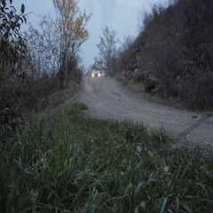 Car is going through an off-road in twilight Stock Footage