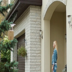 Smiling Woman Stands on a Porch While Flying Drone Delivers Her Postal Package t Stock Footage