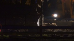 Excavator aligns ground at night with the lights on Stock Footage