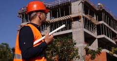 Inspector Workplace Engineer with Scheme Plan Looking Out Unfinished Building Stock Footage