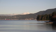 A picturesque scene of the tranquil waters of English Bay & Stanley Park at dawn Stock Footage