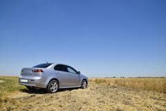 The car, standing on the edge of a wheat field Stock Photos
