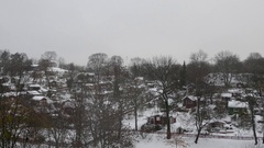 Right to left pan over a small village on mountain during a snowy day Stock Footage