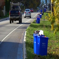 Recycle boxes roadside with traffic, medium shot Stock Footage